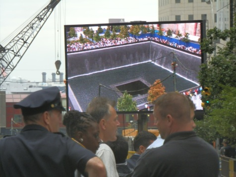 Images of the new 9/11 Memorial and victims' parents and loved ones reading their names display on a large screen in Zuccotti Park.
