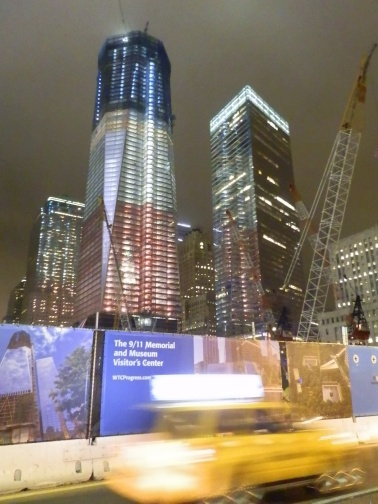 The new 1 World Trade Center, under construction, aglow in red, white, and blue. From the corner of Church and Dey streets.