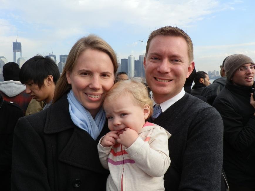 Susan, Fiona, and Dustin on the Statue of Liberty/Ellis Island ferry with Lower Manhattan in the background, 31 December 2011.