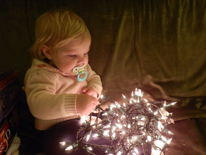 Fiona plays with a string of lights as we take down our tree on 7 January 2011.