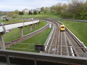 A PRT vehicle speeds along tracks bypassing Engineering station.