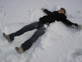 Susan demonstrates making a snow angel. In this photo, step 1.