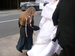 Amanda helps hold the train of Susan's wedding dress.