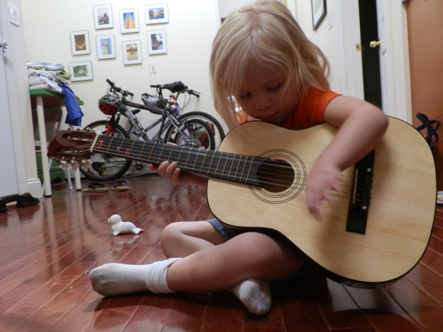 Fiona plays the guitar during circle time. During circle time each morning, we say a prayer, talk about the calendar and weather, and sing songs.