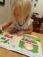 Fiona works on a workbook during homeschool preschool.