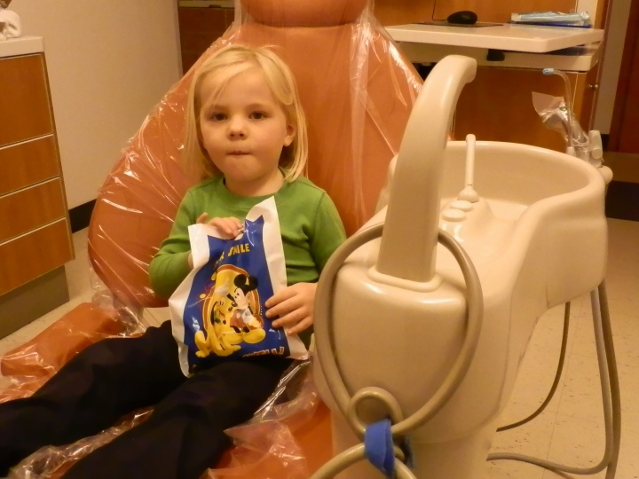 Fiona sits in the big orange chair with her bag of goodies as she gets ready to leave the dentist's office.