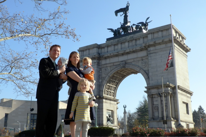 "Dustin holds Heath, Susan holds Colin, and Fiona holds Gupper (or ""Gupr"", as she spells it) in front of the Memorial Arch at Grand Army Plaza, Brooklyn, New York, 6 December 2015."