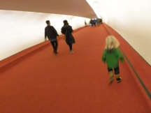 Fiona and her green raincoat stand out against the red carpeting and white walls of one of the two tube-shaped corridors that connected the head house to the original gates. The southern tube dates from the original 1962 Saarinen structure while the northern one, seen in this photo, was added in 1969 as part of Flight Wing One by architects Kevin Roche and John Dinkeloo.